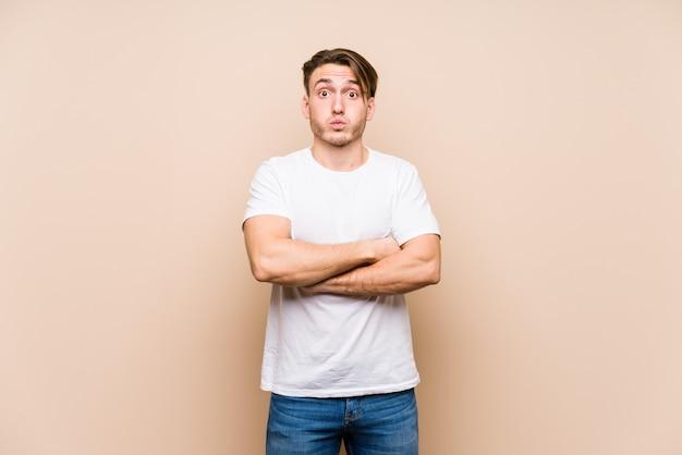 Jeune homme caucasien posant isolé coups joues, a une expression fatiguée. concept d'expression faciale.