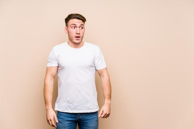 Jeune homme caucasien posant isolé étant choqué à cause de quelque chose qu'elle a vu.