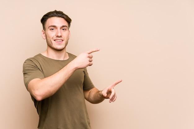 Jeune homme caucasien posant isolé excité pointant avec les index loin.