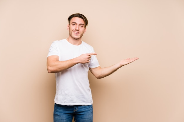 Jeune homme caucasien posant isolé excité tenant un espace de copie sur la paume.