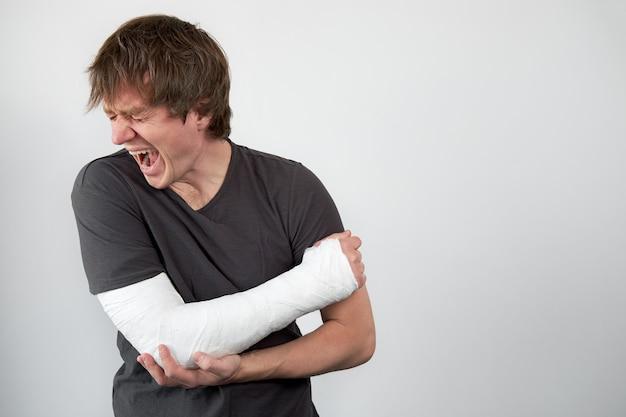 Jeune homme caucasien qui pleure malheureux avec plâtre moulé sur sa main hurlant de douleur.