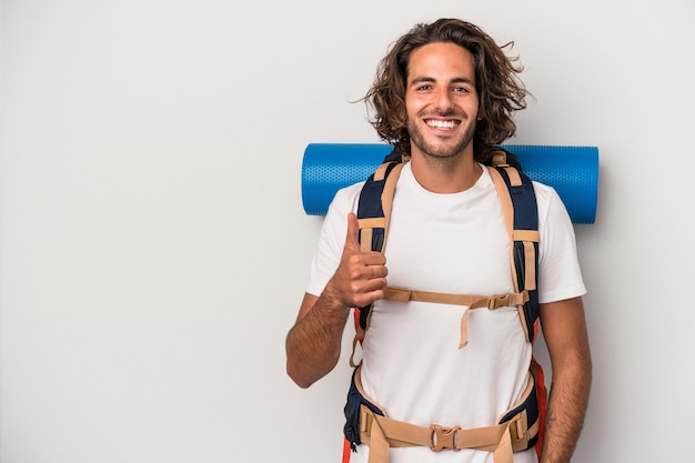 Jeune homme caucasien de randonneur isolé sur fond gris souriant et levant le pouce vers le haut