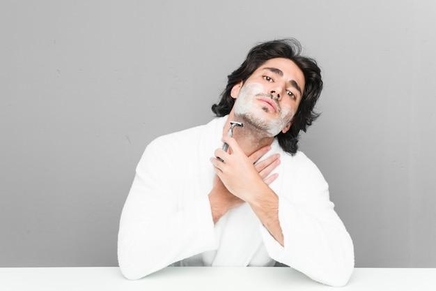 Jeune homme caucasien raser sa barbe isolé sur un mur gris