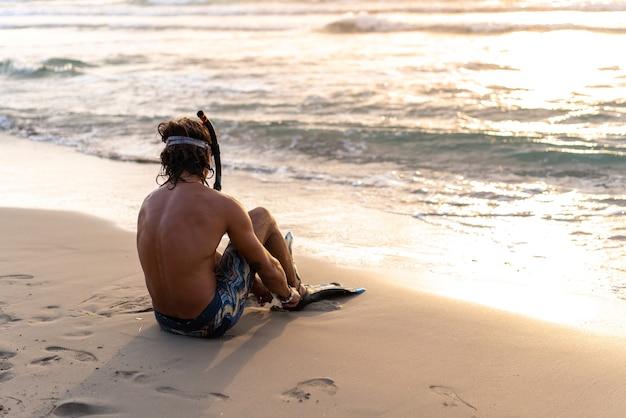 Jeune homme caucasien s'apprête à plonger dans la mer