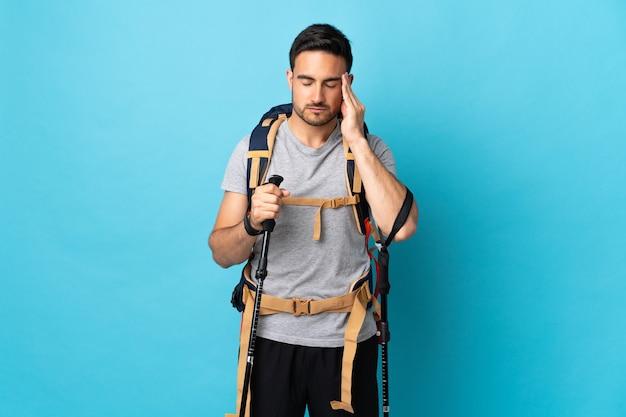 Jeune homme caucasien avec sac à dos et bâtons de randonnée isolés sur bleu avec maux de tête