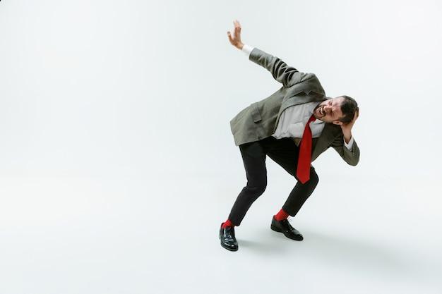 Jeune homme caucasien se déplaçant flexible sur blanc