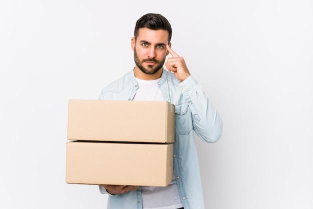 Jeune homme caucasien se déplaçant vers une nouvelle maison isolée du temple de pointage avec le doigt, pensant, concentré sur une tâche