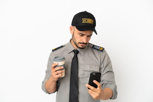 Jeune homme caucasien de sécurité isolé sur fond blanc tenant du café à emporter et un mobile