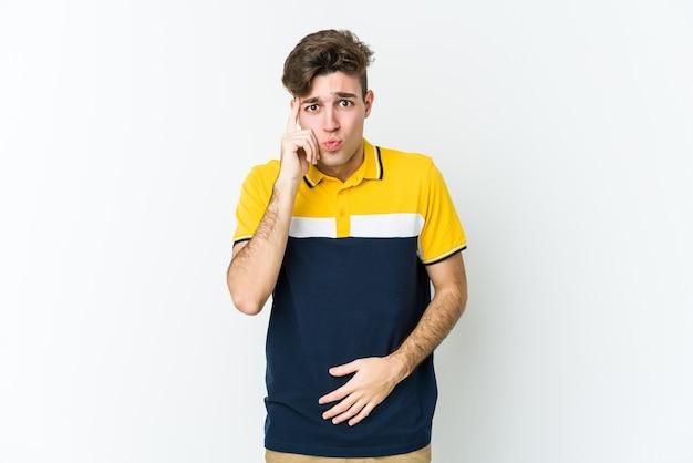 Jeune homme caucasien souffle sur les joues, a une expression fatiguée. concept d'expression faciale.