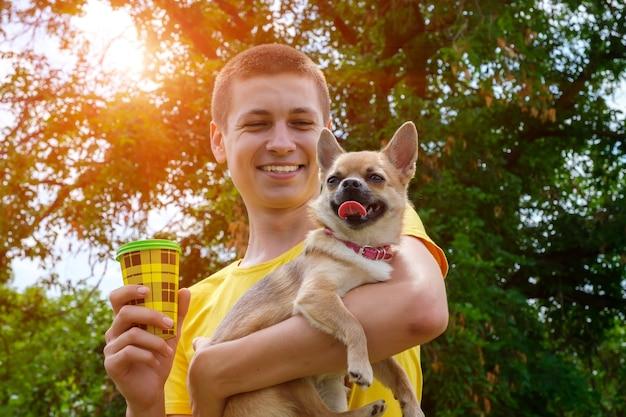 Jeune homme caucasien souriant tenant un chien chihuahua et un café à emporter. balade dans le parc en été, low angle view