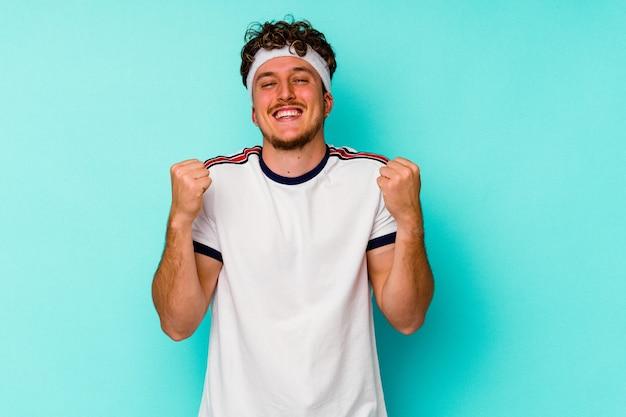 Jeune homme caucasien de sport isolé sur fond bleu applaudissant insouciant et excité. concept de victoire.