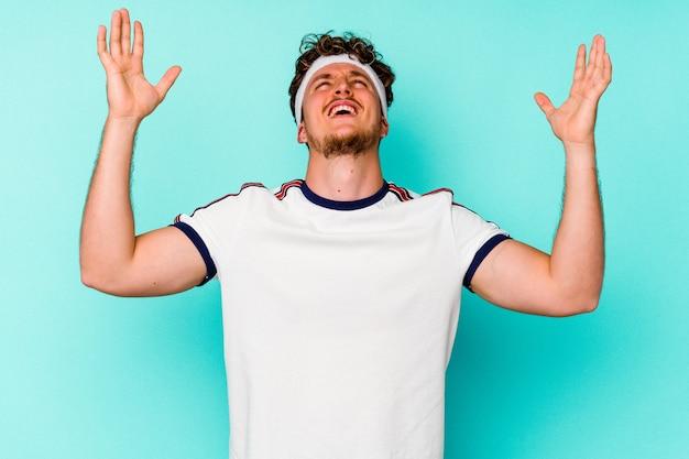Jeune homme caucasien de sport isolé sur fond bleu criant vers le ciel, levant les yeux, frustré.