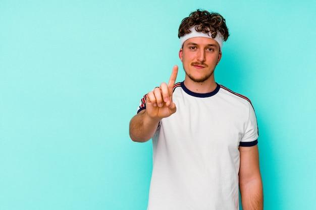 Jeune homme caucasien sport isolé sur fond bleu montrant le numéro un avec le doigt.