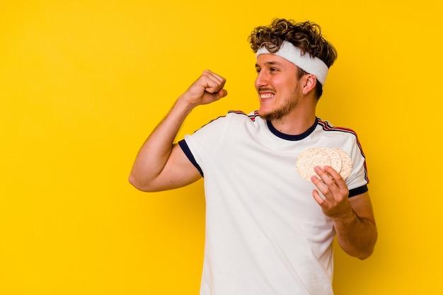 Jeune homme caucasien de sport mangeant un gâteau de riz isolé sur fond jaune levant le poing après une victoire, concept gagnant.