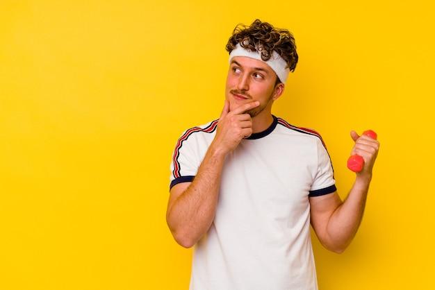 Jeune homme caucasien de sport tenant un haltère isolé sur fond jaune regardant de côté avec une expression douteuse et sceptique.