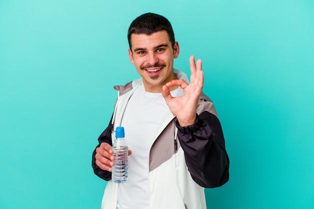 Jeune homme caucasien sportif eau potable isolé sur mur bleu joyeux et confiant montrant le geste ok