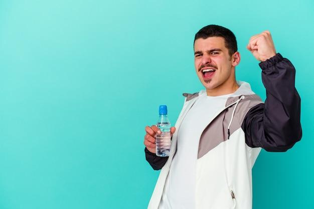 Jeune homme caucasien sportif eau potable isolée sur bleu levant le poing après une victoire, concept gagnant.