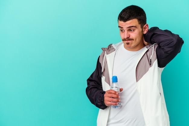 Jeune homme caucasien sportif, eau potable isolée sur mur bleu, toucher l'arrière de la tête, penser et faire un choix.