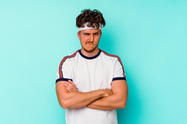 Jeune homme caucasien sportif isolé sur fond bleu, fronçant les sourcils de mécontentement, garde les bras croisés.
