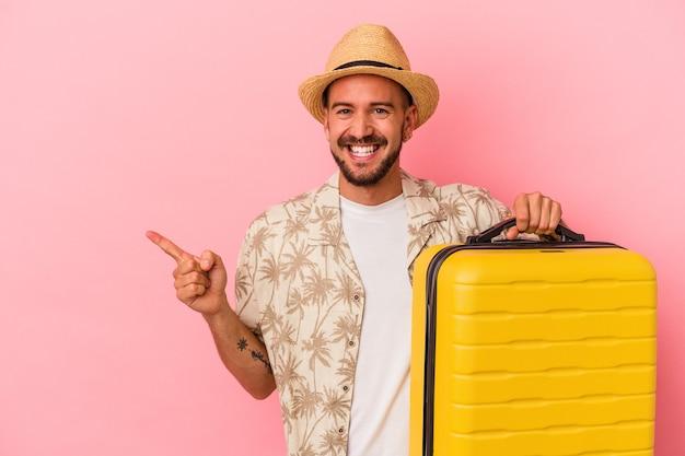 Jeune homme caucasien avec des tatouages allant voyager isolé sur fond rose souriant et pointant de côté, montrant quelque chose dans un espace vide.