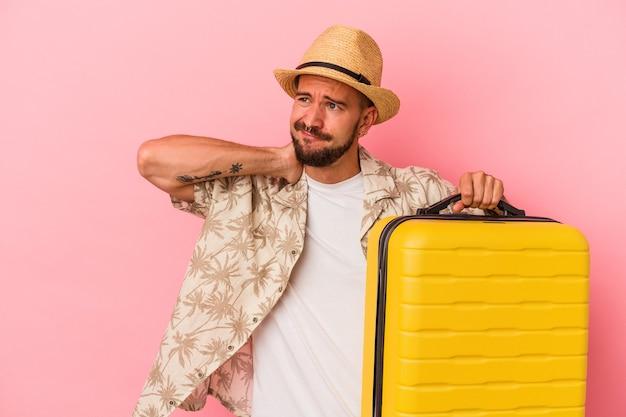 Jeune homme caucasien avec des tatouages allant voyager isolé sur fond rose touchant l'arrière de la tête, pensant et faisant un choix.