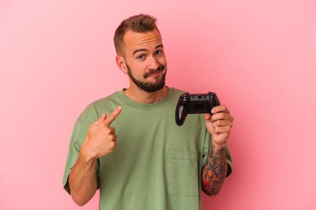 Jeune homme caucasien avec des tatouages tenant un contrôleur de jeu isolé sur fond rose pointant le doigt vers vous comme s'il vous invitait à vous rapprocher.