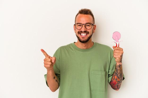 Jeune homme caucasien avec des tatouages tenant une sucette isolée sur fond blanc souriant et pointant de côté, montrant quelque chose dans un espace vide.