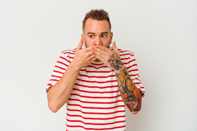 Jeune homme caucasien tatoué isolé sur fond blanc choqué couvrant la bouche avec les mains.