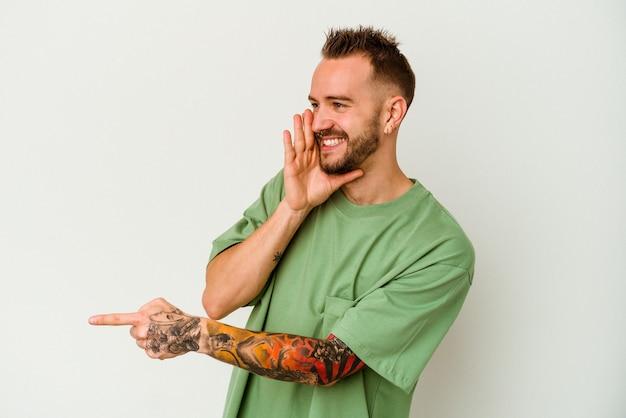 Jeune homme caucasien tatoué isolé sur fond blanc disant un potin, pointant vers le côté rapportant quelque chose.