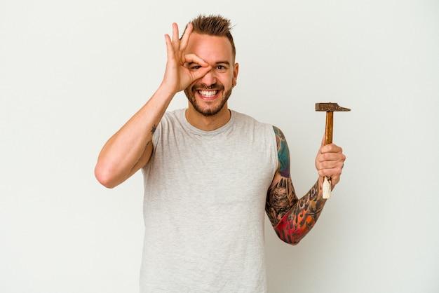 Jeune homme caucasien tatoué isolé sur fond blanc excité en gardant le geste ok sur les yeux.