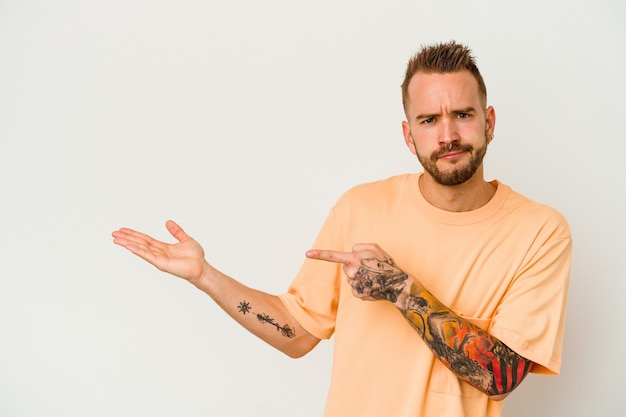 Jeune homme caucasien tatoué isolé sur fond blanc excité tenant un espace de copie sur la paume.
