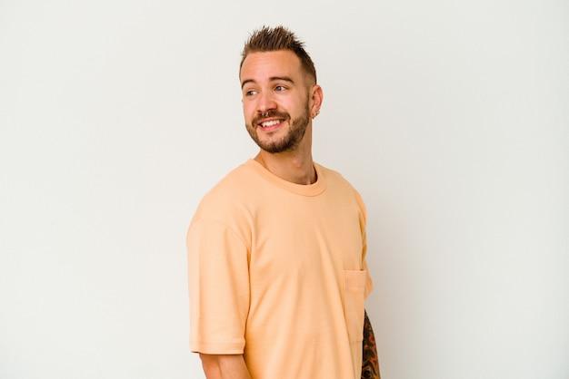 Jeune homme caucasien tatoué isolé sur fond blanc regarde de côté souriant, joyeux et agréable.