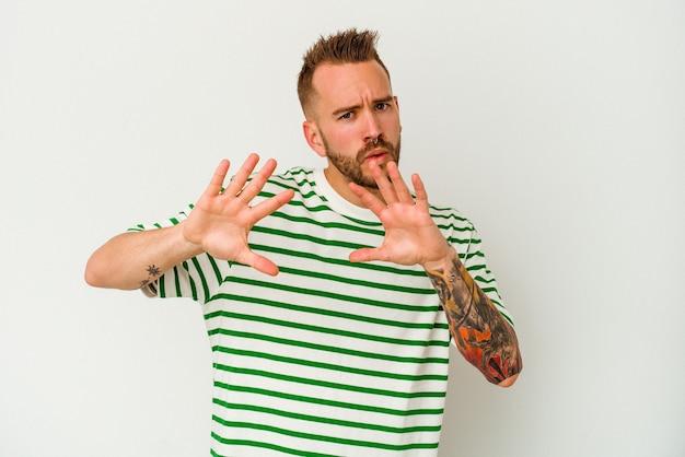 Jeune homme caucasien tatoué isolé sur fond blanc rejetant quelqu'un montrant un geste de dégoût.
