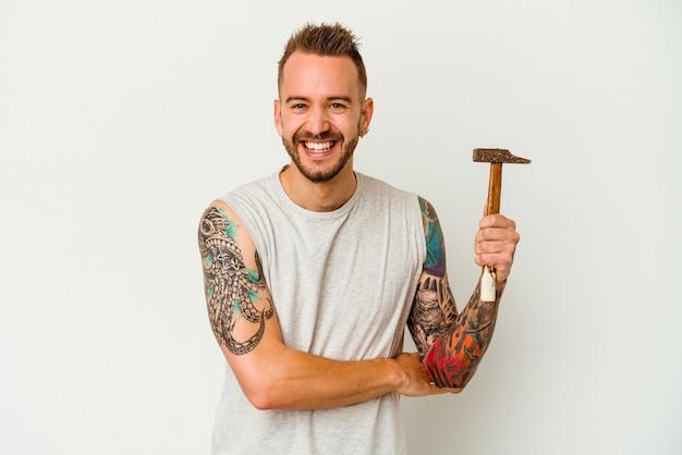 Jeune homme caucasien tatoué isolé sur fond blanc en riant et en s'amusant.