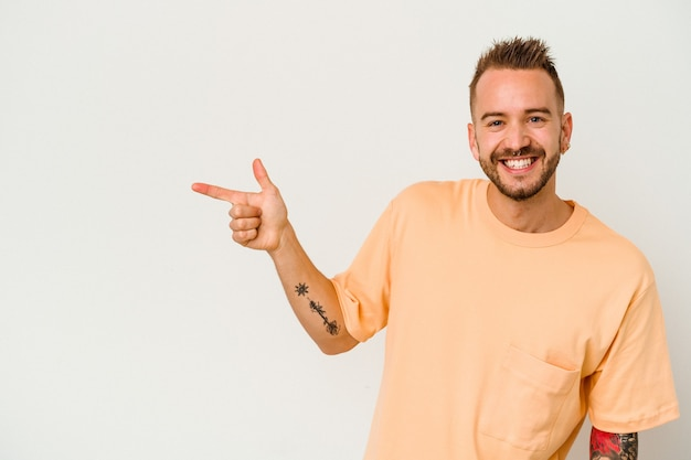 Jeune homme caucasien tatoué isolé sur fond blanc souriant joyeusement pointant avec l'index loin.