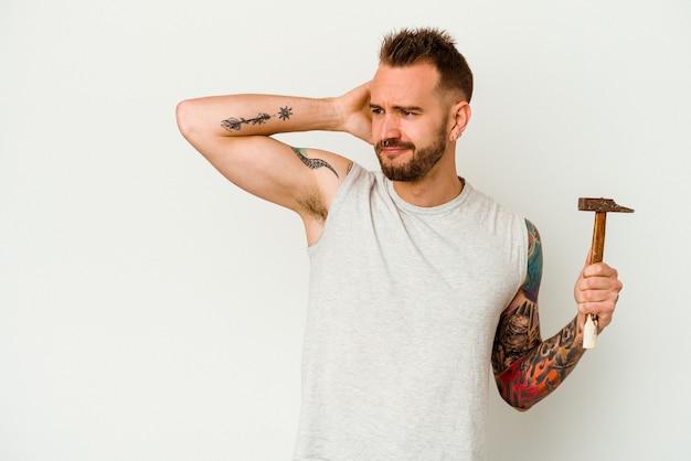 Jeune homme caucasien tatoué isolé sur fond blanc, toucher l'arrière de la tête, penser et faire un choix.