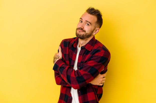 Jeune homme caucasien tatoué isolé sur fond jaune câlins, souriant insouciant et heureux.