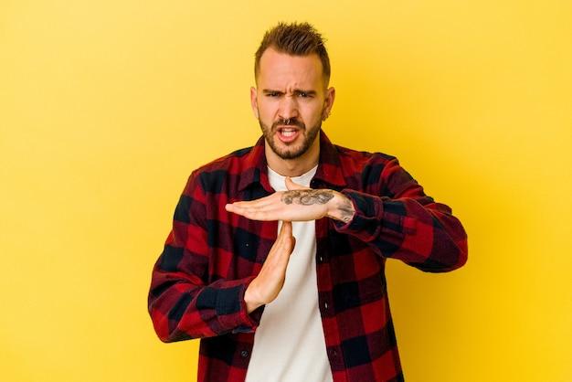 Jeune homme caucasien tatoué isolé sur fond jaune montrant un geste de temporisation.