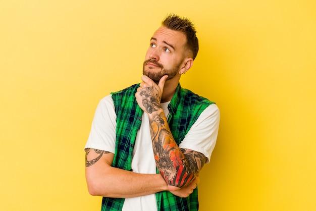 Jeune homme caucasien tatoué isolé sur fond jaune pensant et levant, réfléchissant, contemplant, ayant un fantasme.