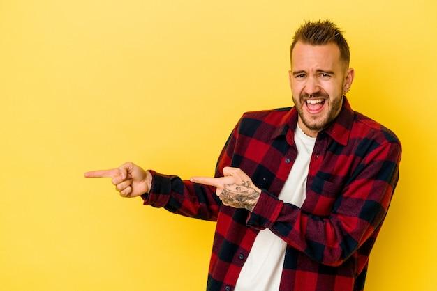 Jeune homme caucasien tatoué isolé sur fond jaune pointant avec l'index vers un espace de copie, exprimant l'excitation et le désir.