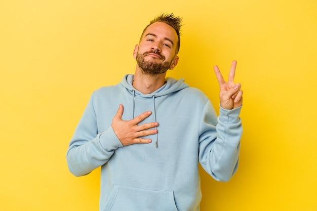 Jeune homme caucasien tatoué isolé sur fond jaune en prêtant serment, mettant la main sur la poitrine.