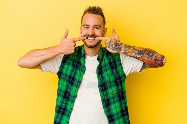 Jeune homme caucasien tatoué isolé sur fond jaune sourit, pointant du doigt la bouche.