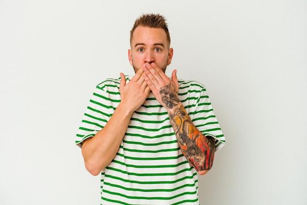 Jeune homme caucasien tatoué isolé sur un mur blanc choqué couvrant la bouche avec les mains.