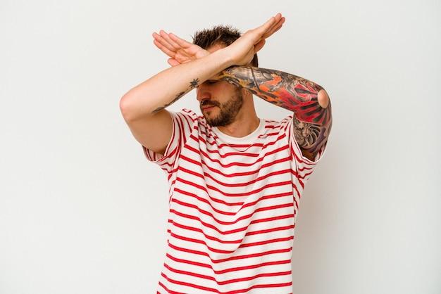 Jeune homme caucasien tatoué isolé sur un mur blanc gardant deux bras croisés, concept de déni.