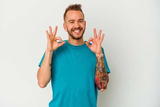 Jeune homme caucasien tatoué isolé sur un mur blanc joyeux et confiant montrant un geste correct.