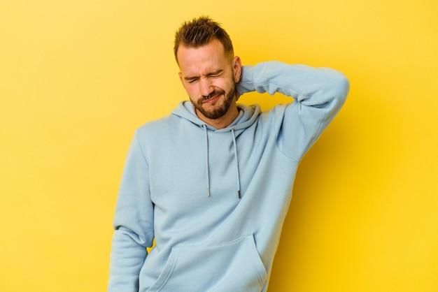 Jeune homme caucasien tatoué isolé sur un mur jaune ayant une douleur au cou due au stress, en massant et en le touchant avec la main.