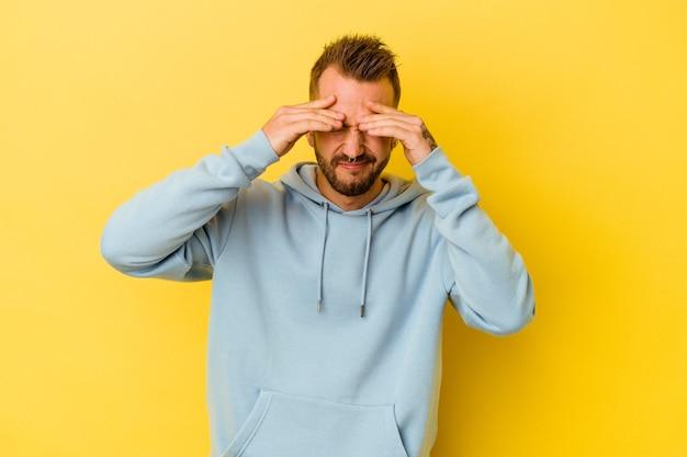 Jeune homme caucasien tatoué isolé sur un mur jaune ayant mal à la tête, touchant l'avant du visage.
