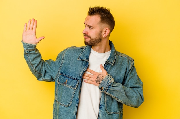 Jeune homme caucasien tatoué isolé sur un mur jaune en prêtant serment, mettant la main sur la poitrine.