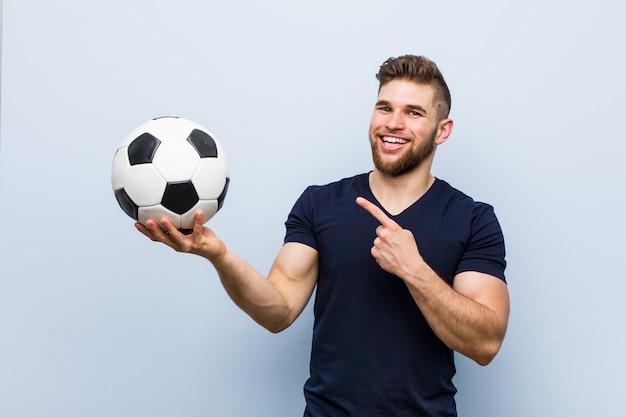 Jeune homme caucasien tenant un ballon de soccer souriant joyeusement pointant avec l'index loin.