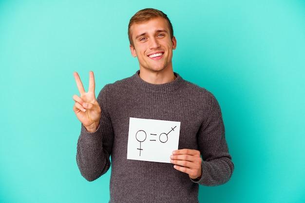Jeune homme caucasien tenant une bannière d'égalité des sexes isolée sur bleu